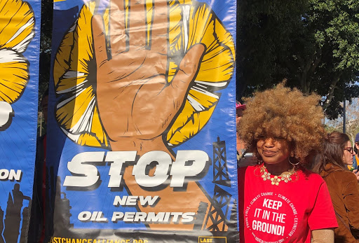 Unique Vance standing next to a large colorful banner that reads 'Stop New Oil Permits'